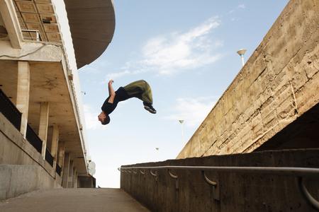 若い男は、後ろ宙返りを行います。都市空間におけるパルクール。市内のスポーツ。スポーツ活動。 写真素材