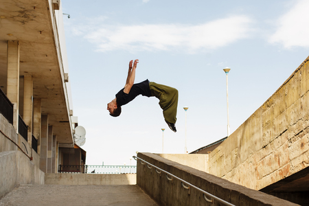 Young man back flip. Parkour in the urban space. Sport in the city. Sport Activities outdoors. Acrobatics Banco de Imagens