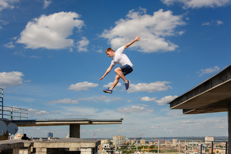 A man is jumping from roof to roof. Parkour. Active lifestyle. Courage. Adrenalin. Roofer Archivio Fotografico