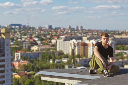 edges: The roofer rests after climbing to the roof. Active way of life in urban space. Courage and adrenaline. Stock Photo