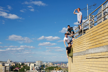 edges: A group of roofer climbs the stairs to the roof. Active way of life in urban space. Courage and adrenaline. Stock Photo
