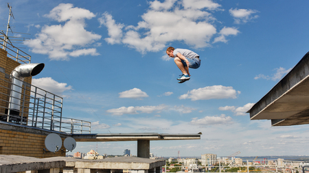 A man is jumping from roof to roof. Parkour. Active lifestyle. Roofer