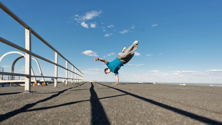 Roofer stands on hands on the edge of the roof. Extreme acrobatics. Courage and adrenaline. Parkour and Roofing. Stockfoto