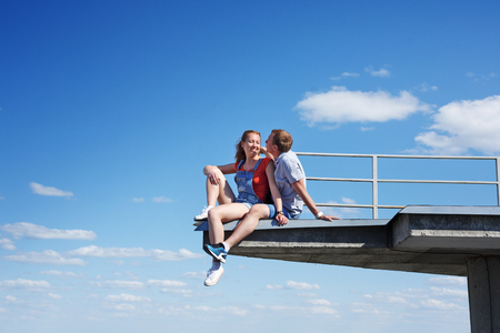 roofer couple in love sitting on the edge of the roof. Romance and courage. An unusual date. Stock Photo