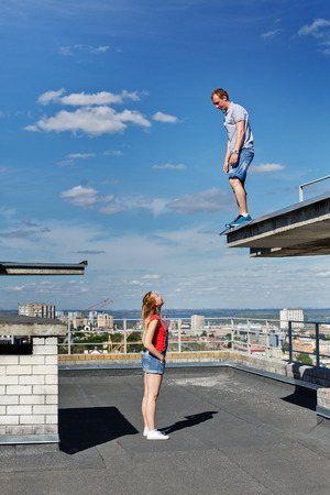 A loving couple of roofer on the roof. The guy and the girl are looking at each other. Romance and courage. An unusual date.