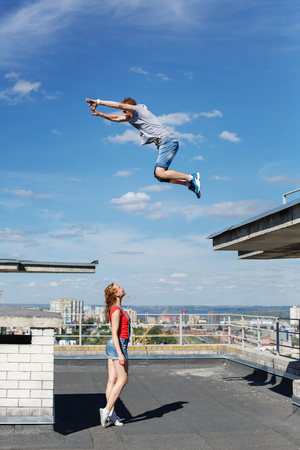 A loving couple of roofer on the roof. The girl watches as her boyfriend jumps from roof to roof. Romance and courage. An unusual date. Stock Photo