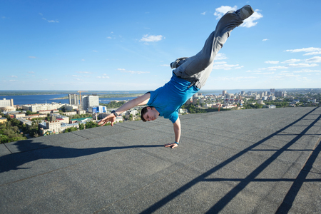 peace risk: Roofer stands on his hands on the edge of the roof. Extreme acrobatics. Courage and adrenaline. Parkour and Roofing. Stock Photo