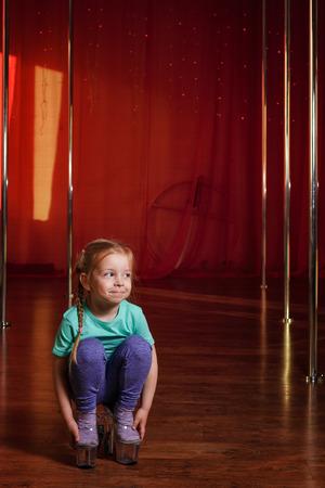 une petite fille dans des chaussures à talons hauts . elle est dans la salle de bal de danse