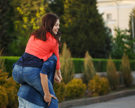 Guy rolls his girlfriend Piggyback. Enamored teenagers on a date. Fun and romance of the first date.