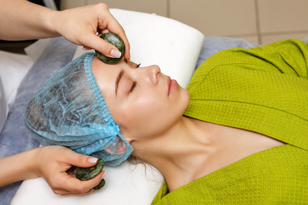 Spa treatment. Facial massage with jade stones. Alternative medicine. Massage of forehead zone. Guasha Stock Photo