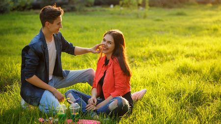 A loving couple of teenagers. Sudden picnic in the park at sunset. Teenagers are sitting on the lawn. Theyre talking and smiling. Stock Photo