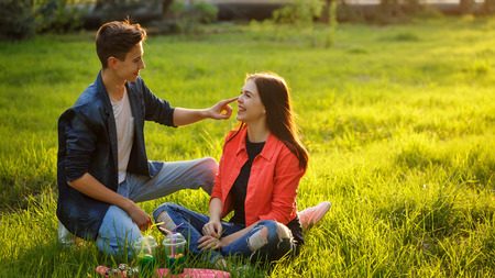 A loving couple of teenagers. Sudden picnic in the park at sunset. Teenagers are sitting on the lawn. They talk and smile. Stock Photo