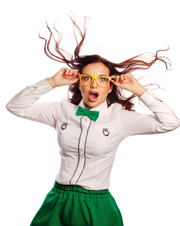 Young attractive girl in blouse, glasses and bow tie. She is surprised, delighted and joyful. Modern fashion. Business style. The season of discounts. Flying hair