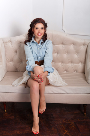 Young attractive girl is sitting on the couch. She smiles. Home cosiness. The girl is barefoot.