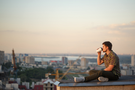 A man drinks coffee early in the morning on the roof. He looks away and thinks. In the background, the city landscape Reklamní fotografie