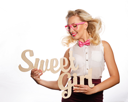 Young attractive girl holding an inscription of a sweet girl. She is wearing a blouse, a bow tie and glasses. Stock Photo