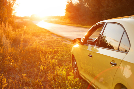 The yellow car is on the side of the road. The road passes through the forest. On the skyline of the setting sun can be seen.