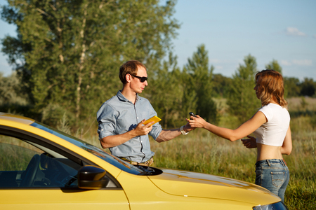 auto repair: Couple in love. Road adventure. The girl gives the boyfriend the keys of the ignition. They are standing by the car. Stock Photo
