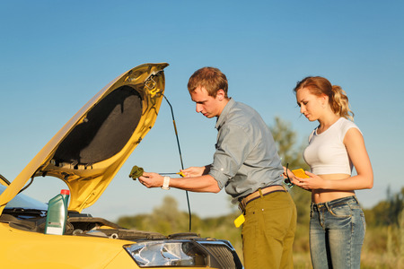 Couple in love. Road Trip. The guy checks the oil level. The girl looks at what he is doing.