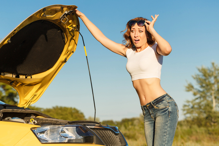 auto repair: A young attractive girl opened the hood of the car and was trying to figure out the breakdown. Trouble on the road.