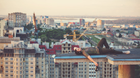 balcony: A hipster guy drinks wine from a bottle on the roof of a high-rise building in the city center. He relaxes after a days work and lies on the roof. Stock Photo