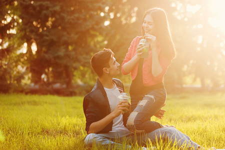 A loving couple of teenagers. Sudden picnic in the park at sunset. Teens drink soft drinks, sitting on the lawn. They look into each others eyes. Stock Photo