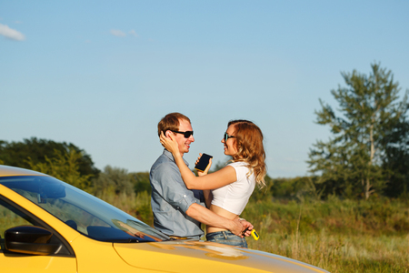 auto repair: Couple in love. Road Trip. The guy hugs his girlfriend. The girl is holding a cell phone. They are standing by the car Stock Photo