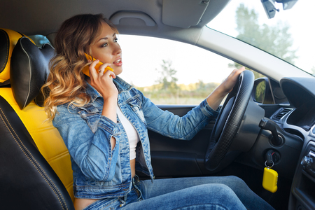 Young attractive girl talking on cell phone. She sits behind the wheel of the car. Urgent call.