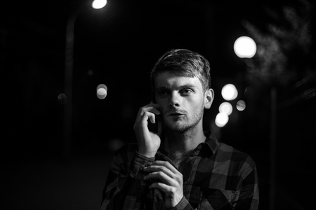 Night portrait of a hipster man. Dramatic light. He wears a plaid shirt and talks on his cell phone. Lights of the night city in the background. Black and white photography Stock Photo