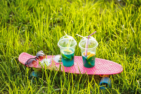Two fruit cocktails stand on the skateboard. Sunglasses lie on the skateboard. Skate stands in the green grass. A refreshing drink.