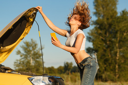 waiting phone call: A young attractive girl opened the hood of the car and makes a video call on the cell phone. Trouble on the road. She is waiting for the tow truck