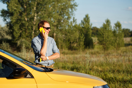 A man is talking on his cell phone. He stands next to the yellow car. Communication in the journey.