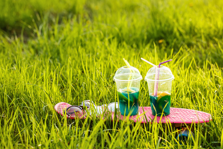 Two fruit cocktails stand on the skateboard. Sunglasses lie on the skateboard. Skate stands in the green grass. Refreshing drink on a hot summer day