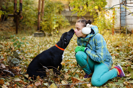 A girl kisses a black mongrel dog. Autumn day. Caring for animals