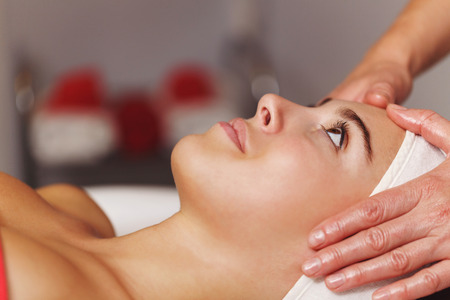 Spa treatment. Face massage. Massage of the forehead and temporal lobe of the client.