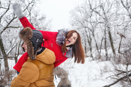 Couple in love. Teenagers on a date outdoors in the winter. He has a girlfriend on his shoulder. They are fooling around. She laughs. The joy of first love. Stock Photo