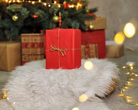 A big red gift stands under the Christmas tree. Background for the holiday. Stock Photo