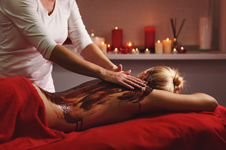 Spa treatment. Back massage with a moisturizing mask. The process of applying the mask. Deep moisturizing and restorative procedures. Chocolate Body Scrub