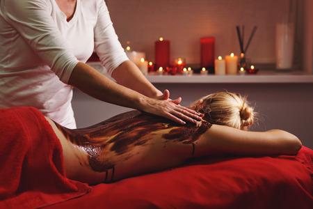 Spa-Behandlung. Rückenmassage mit einer feuchtigkeitsspendenden Maske. Der Vorgang des Aufbringens der Maske. Feuchtigkeitsspendende und erholsame Behandlungen. Schokoladen-Körperpeeling