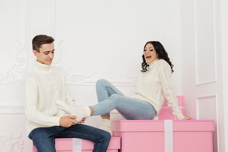 Loving couple teenagers sitting on gifts. He straightens the sock on her leg. Holidays. Happy New Year. Merry Christmas. Valentines Day. Birthday. Фото со стока
