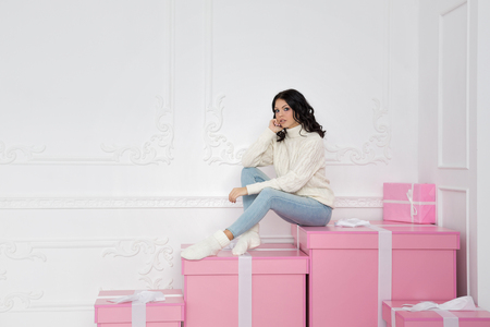 Young cute teenage girl in a knitted white sweater and socks. She sits on a big pink gift and is sad. Holidays. Happy New Year. Merry Christmas. Valentines Day. Birthday.