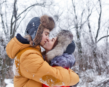 Couple in love. Teenagers on a date outdoors in the winter. They hold each other tightly. Boyfriend and the girlfriend are kissing. The joy of first love. Stock Photo