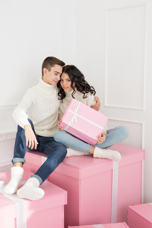 A loving couple of teenagers are sitting on presents. Man hugging girlfriend. She is holding a pink gift in her hands. Holidays. Happy New Year. Merry Christmas. Valentines Day. Birthday.