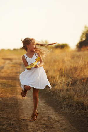 A little girl in a white dress and sandals runs along a country road. She holds a toy in her hands. Happy childhood. Summer vacation