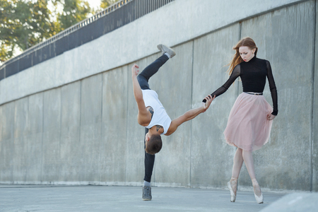 A young ballerina and a parkour man dance in the streets of the city. The girl is holding the guy by the hand. He flips forward. An unusual couple in love. Date dancers