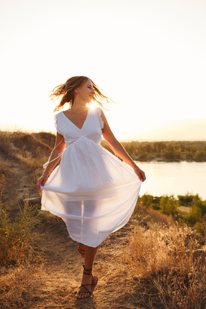 A young girl in a white dress is walking along a path along the river. She is wearing a white dress. In the blonde hair, the setting sun is visible. Stockfoto