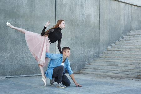 Slender ballerina dances with a modern dancer. Dating lovers. Performance in the streets of the city.
