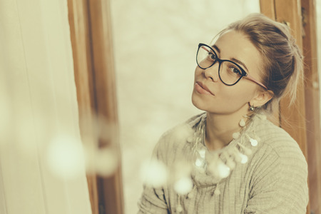 Portrait of a cute girl in glasses at the window. Festive garland in the frame.