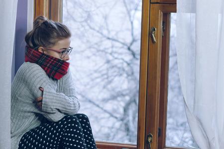 眼鏡をかけた少女と窓際の暖かいスカーフの肖像画。寒さ彼女は春の訪ねを待っている 写真素材