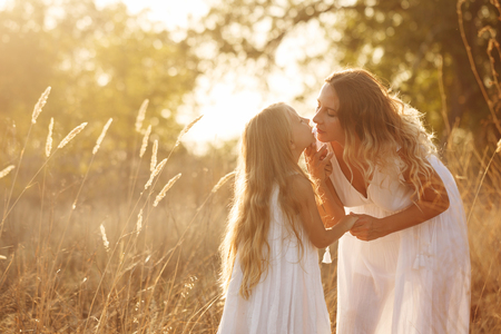 Family, mother and daughter are walking in the meadow at sunset. Mother bent to kiss the little girl. They are blondes. Family time together. Stock Photo